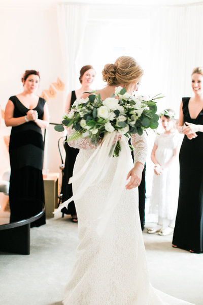 A bride twirls in her wedding dress as she has a moment with her bridesmaids.