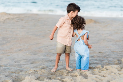 Young brother and sister standing on the beach hugging