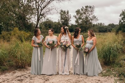 A bride and her bridesmaids standing on the beach hold wedding flower bouquets and the bride wearing a flower crown