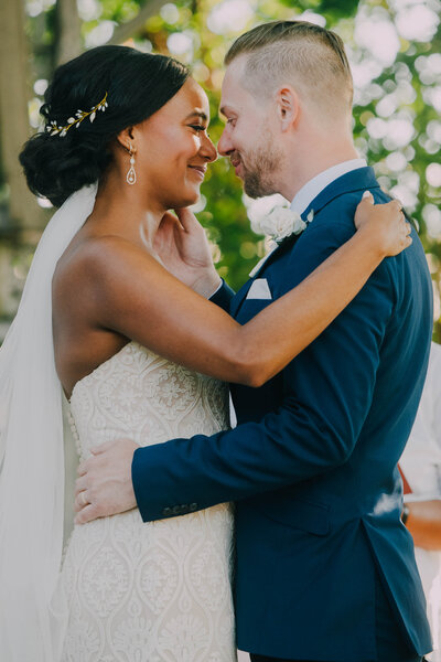 bride in white dress with veil and metal flower crown tears up after first kiss with groom in blue tux at terrain in glen mills shot by philadelphia wedding photographer alex medvick