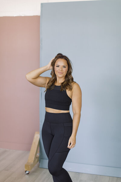 Brooke poses wearing all black Zyia Active apparel