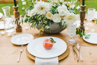 peach sitting on white plate in front of flowers