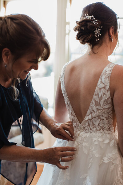 Mom helping bride zip on wedding dress at the Pierce house