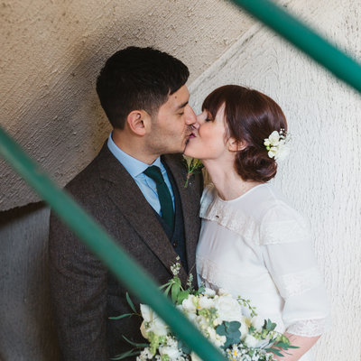 Vintage styled bride and groom kissing in a stairwell at St Albans Registry Office