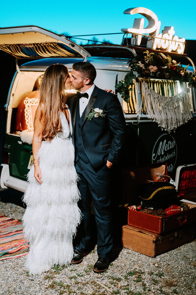 Lux boho couple kisses in front of photobooth van on their wedding day