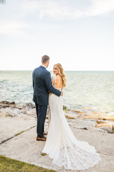 bride and groom standing near lake michigan