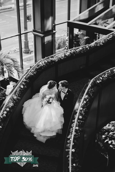 Bride and Groom sitting on the stairs of the Amway hotel in Grand Rapids