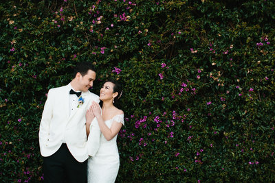 Bride and Groom smiling in front of green foliage at their Malibu wedding