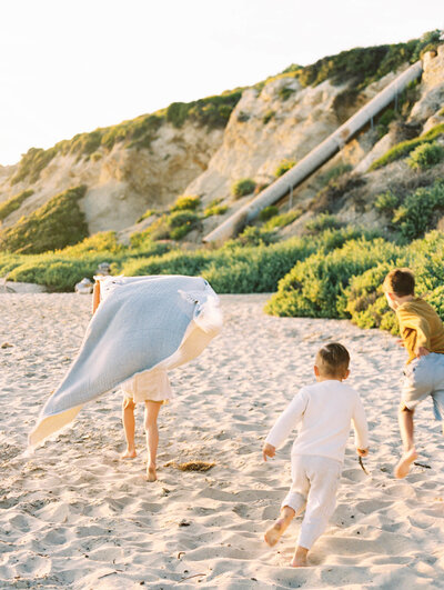 candid moment during a family photo on the beach in california