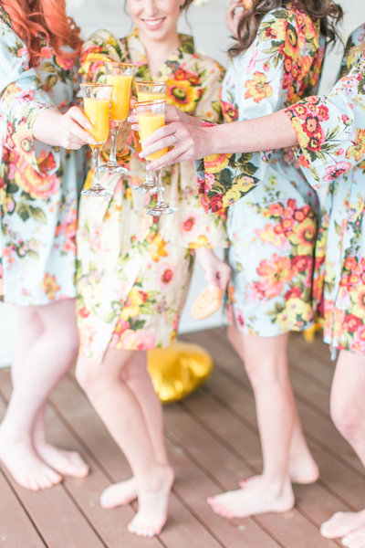 bridal party in flower robes and toast mimosas