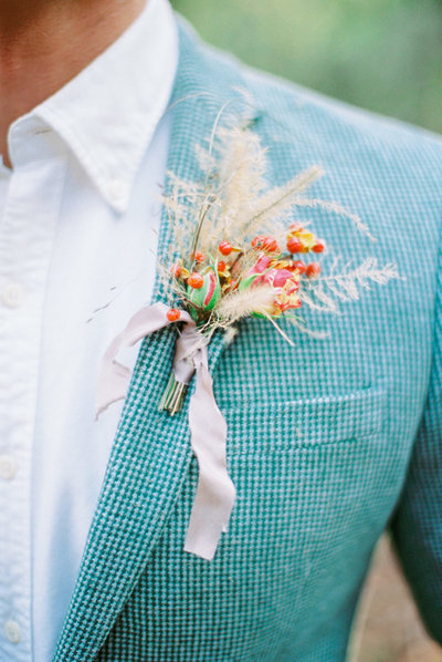 Berry-filled boutonniere with a raw silk ribbon