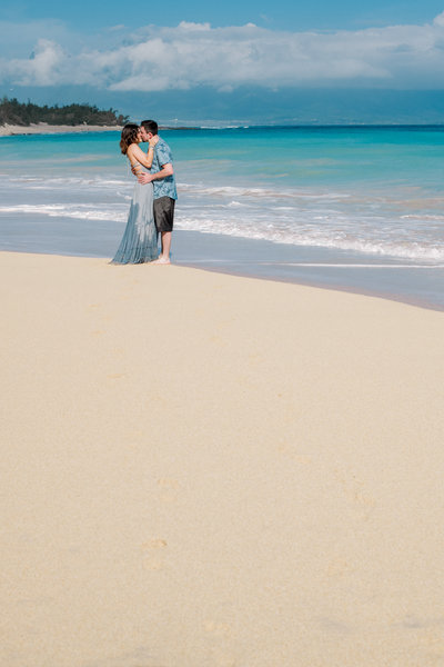 Couple kisses along blue ocean water in Paia Maui.