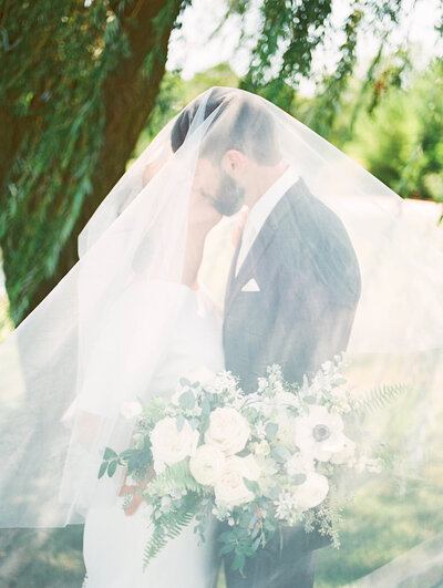 couple kiss under veil after getting married in Northern Indiana photography by Grand Rapids wedding photographer Cynthia Boyle