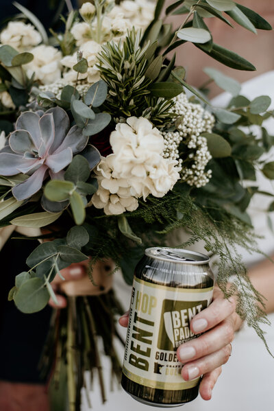 bride holding flowers and beer