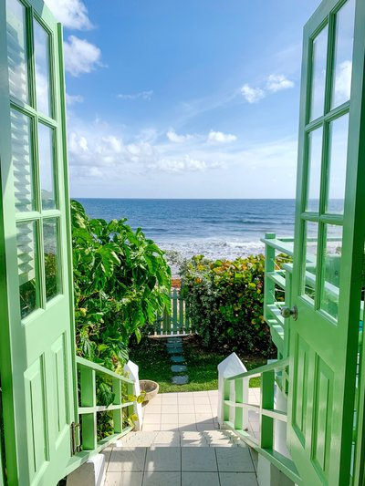 The view from Candice's favorite beach house, with green doors opening to a view of the caribbean sean