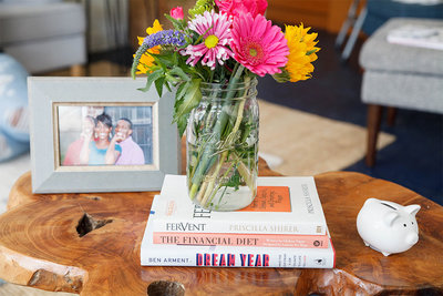 Flowers in a mason jar sitting ontop of a stack of books with a fram on the left.