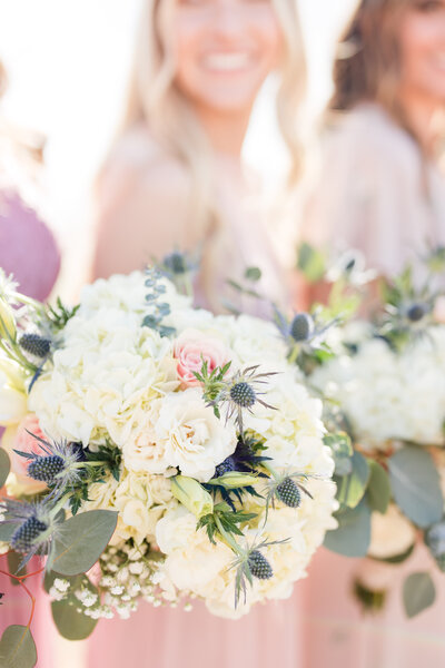 A bridesmaid's bouquet with smiling bridesmaid out of focus behind