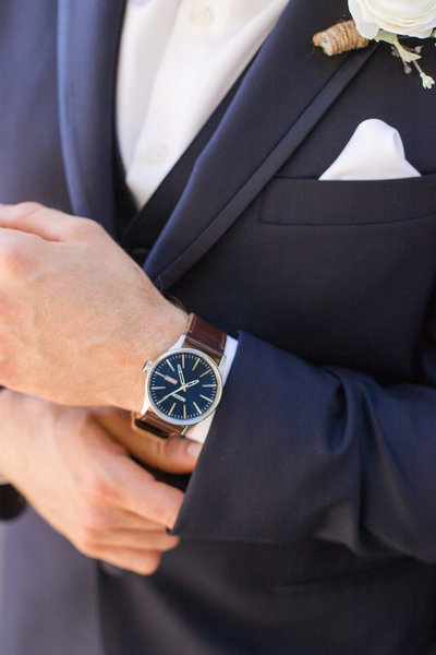 A groom poses showing of his luxury watch at a downtown Sacramento wedding.