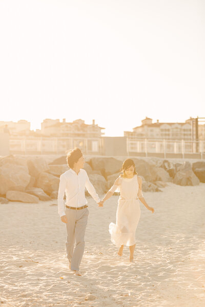 Man leads his future bride in the sand of a beach during engagement session