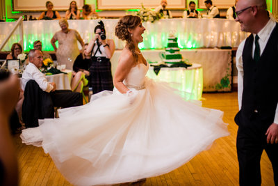 Bride twirls her dress while she and groom dance at their Masonic Temple wedding in Erie PA