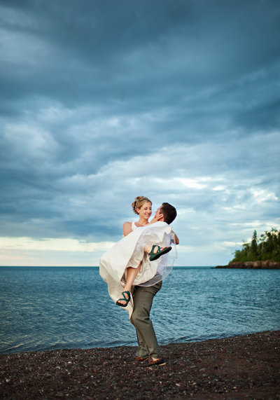 A groom is holding up his bride on the North Shore of Lake Superior.