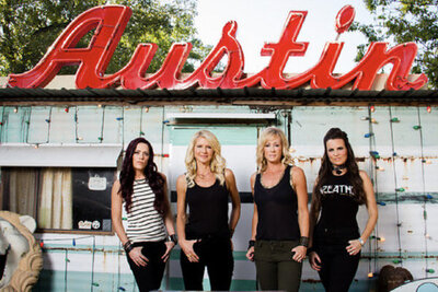 Band portrait female music group The Mrs standing against building with the sign Austin written in red above them