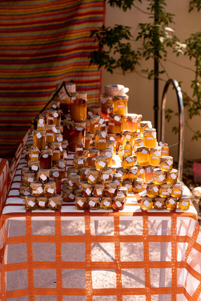 Honey in glass jars stacked on a table with red and white table cloth