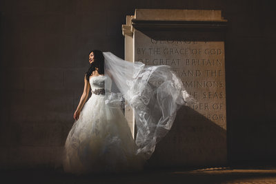 a bride wearing a vera wang wedding dress outside the midland hotel in manchester with veil flowing in the wind. photographed in harsh direct sunlight