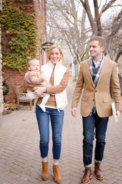 family photograph of mother, father, and baby walking in a small town village
