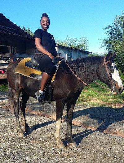 Melanie Grandoit smiling and sitting on a dark brown horse getting ready to go horseback riding in Helen, GA.