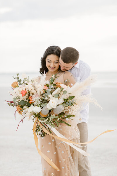 Bride and groom embrace with elaborate bouquet on the beach during their elopement