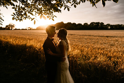 bride-and-groom-looking-at-each-other-at-sunset-tithe-barn