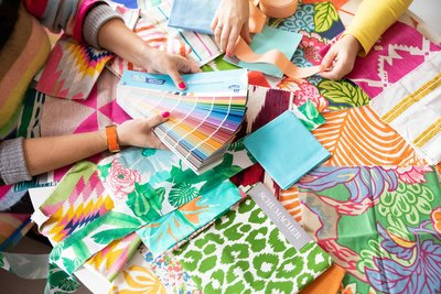 Two sets of hands look through colorful swatches and fabrics.