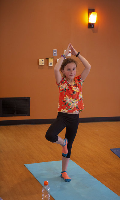 Young girl practices tree pose in yoga class