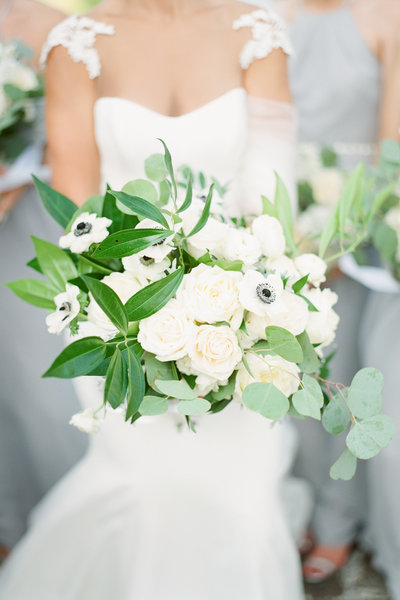 Bride holds out beautiful white floral bouquet