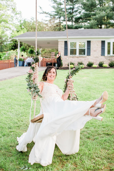 Bride in flowing dress swings on a rope swing smiling in Maryland
