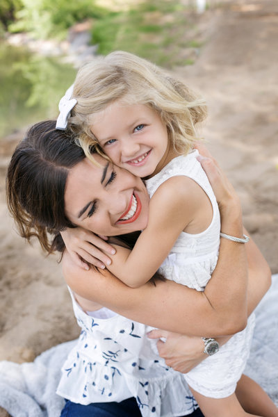 Mom and daughter embracing in a hug during a break in photo session