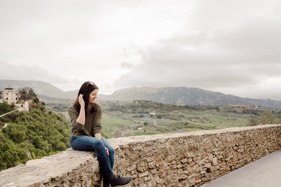 woman sitting on stone wall with mountains in the background