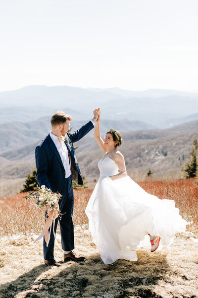 bride and groom dancing on a mountain