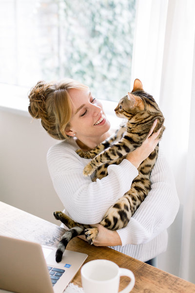 woman smiling holding cat