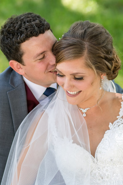 bride and groom laughing while he whispers in her ear