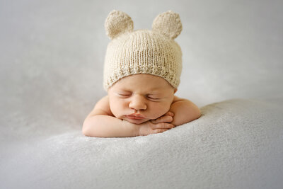 newborn-baby-posed-on-beanbag-with-beautiful-headband