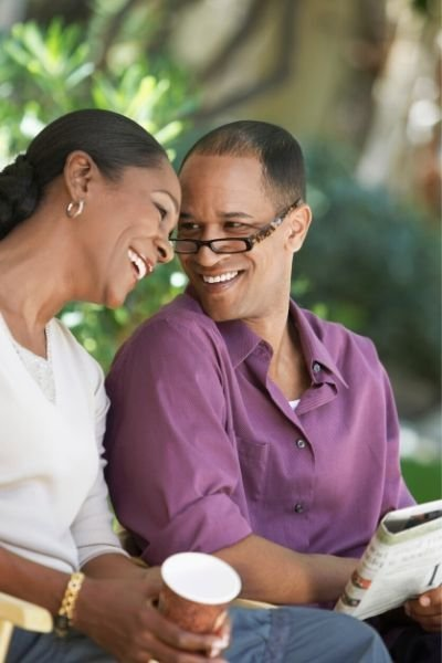 A couple sitting outside smile at one another as they discuss the morning paper. This could symbolize a trusting, loving relationship that has benefited from online therapy in Florida. Contact an online therapist for more information on teletherapy, online marriage counseling, and other services.