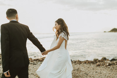 bride and groom holding hands while standing next to ocean