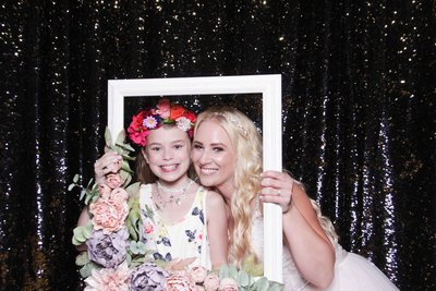 bride and girl posing with a floral frame
