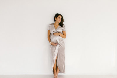 Maternity session with a woman in a long silver dress looking off to the side