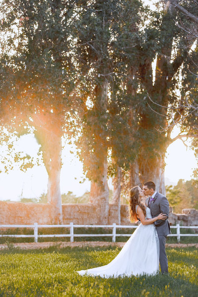 bride and groom embracing at walnut grove wedding venue  during sunset