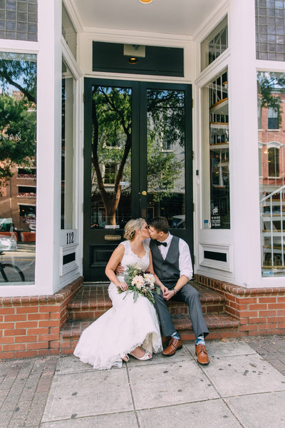 Bride and groom sit on steps of brick building downtown raleigh