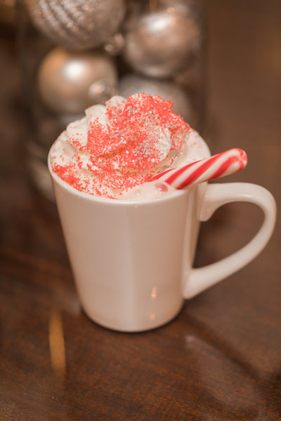 white cup of hot cocoa with peppermint stick at the Golden Horseshoe Inn wedding venue