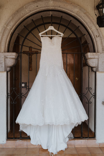 wedding dress hanging in doorway